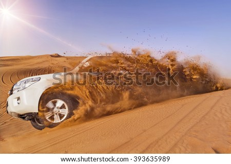 Offroad vehicle bashing through sand dunes in the desert - stock photo