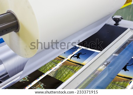 offset machine press print run at table, sheet-fed paper feeder unit. Poster laminator - stock photo