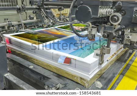 offset machine press print run at table, sheet-fed paper feeder unit. Poster printing - stock photo