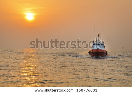 Offshore Boat for Crew Change Before Sunset With Stunning Golden Sky - stock photo