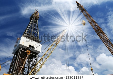 Offshore Drilling Jack Up Rig with Light Beam on Cloudy Day - stock photo