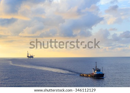 Offshore jack up drilling rig and supply boat in the middle of the ocean during sunset time - stock photo
