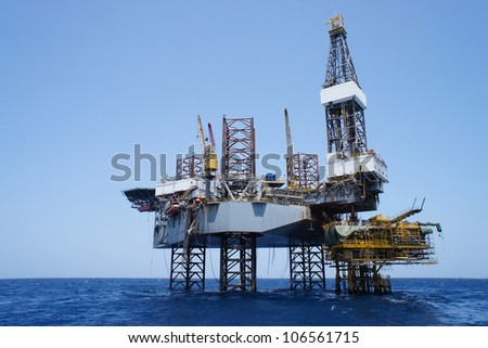 Offshore Jack Up Drilling Rig and The Production Platform in The Middle of The Sea - stock photo