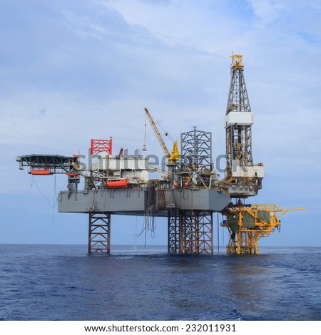 Offshore Jack Up Drilling Rig Over The Production Platform in The Middle of The Sea - View from Crew Boat - stock photo