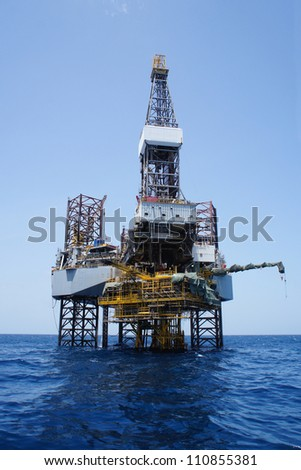 Offshore Jack Up Drilling Rig Over The Top of Oil and Gas Production Platform - stock photo