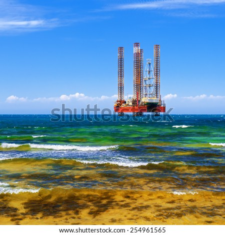 Offshore oil and Gas Production. Drilling platform in the sea against a blue sky - stock photo