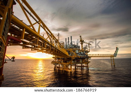 Offshore oil and rig platform in sunset or sunrise time. Construction of production process in the sea. Power energy of the world. - stock photo