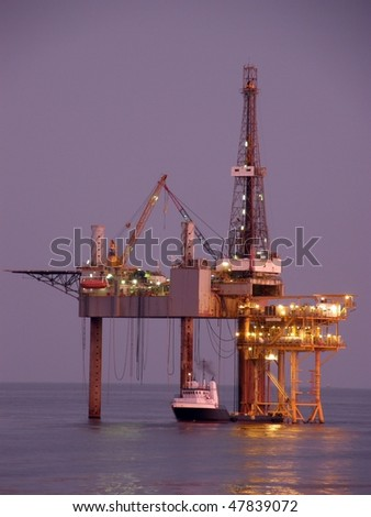 Offshore oil platform, drilling rig, and supply boat at twilight - stock photo