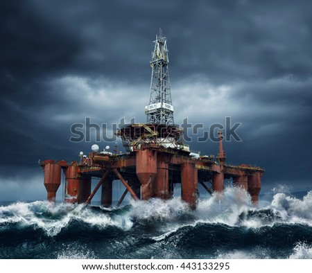 Offshore Oil Platform standing in the middle of ocean sea water during dark cloudy day, with high waves and storm - stock photo