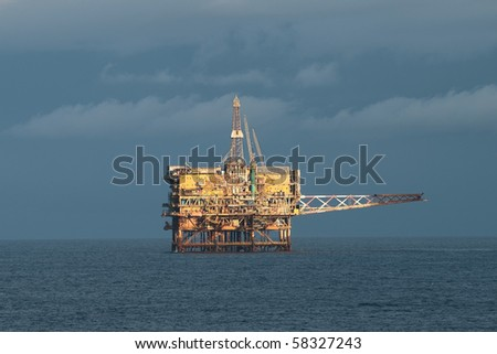 Offshore oil rig in a cloudy day - stock photo