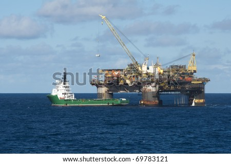 Offshore oil rig transfering container to a supply boat. Campos basin, offshore Rio de Janeiro state, Brazil.  Working for Petrobras oil and gas company. - stock photo
