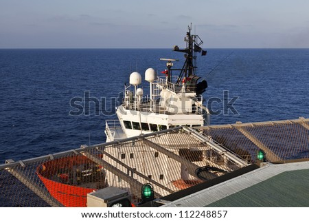 Offshore supply boat under an offshore platform helideck