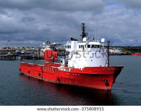 Offshore Supply Vessel in harbor maneuvers. - stock photo