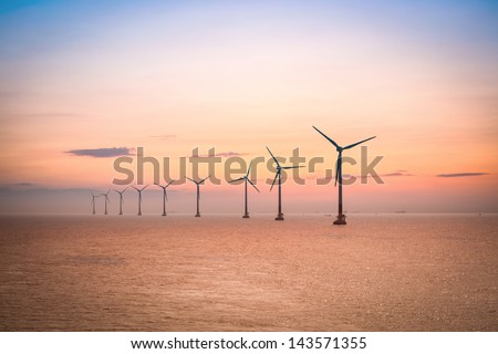 offshore wind farm at dusk in the east China sea. - stock photo