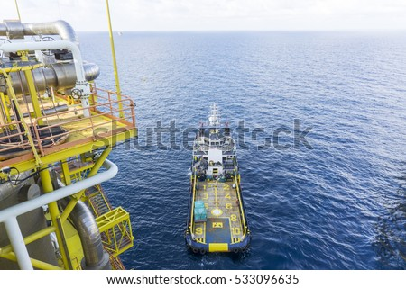 Offshore works. Top view of Supply vessel floating near oil and gas rig platform waiting with marine crew for transferring goods using platform crane.