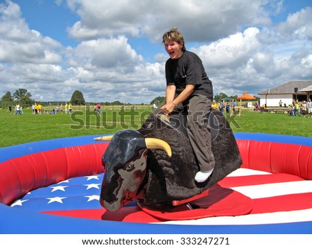 OGRE, LATVIA - JULY 14, 2007: Camping guests have a variety of sports activities. Woman is sitting on jumping artificial electric buffalo back. - stock photo