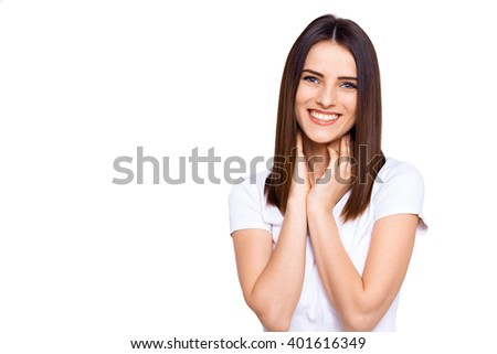 Oh! Beautiful young girl keeping hands on chin and looking on camera while standing against white background - stock photo