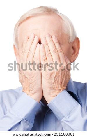 Oh my God!  Frustrated senior man covering his face by hands while standing against white  - stock photo