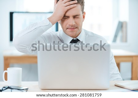 Oh no! Frustrated businessman working on laptop and touching his head while sitting at his working place - stock photo
