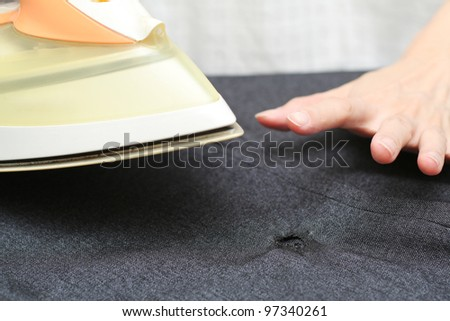 Oh no! I burnt a hole in the garment while ironing! - stock photo