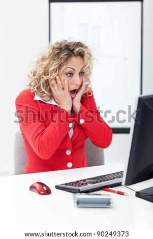 Oh no - shocked business woman in front of computer in the office - stock photo