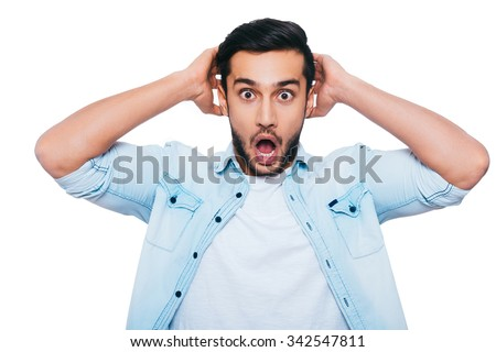 Oh no! Shocked young Indian man holding hands behind head and keeping mouth open while standing against white background - stock photo