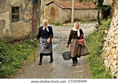OHRID, MACEDONIA, MAY 17, 2011. Two old Macedonian ladies walking up the street in the countryside of Ohrid, Macedonia, on May 17th, 2011.
