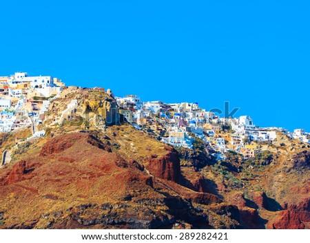 Oia city on volcanic island of Santorini with evening sunlight, Greece. - stock photo