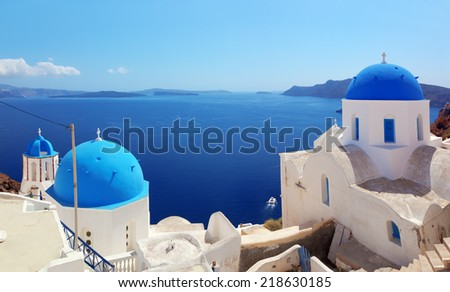 Oia town on Santorini island, Greece. Traditional and famous houses and churches with blue domes over the Caldera, Aegean sea. Panorama