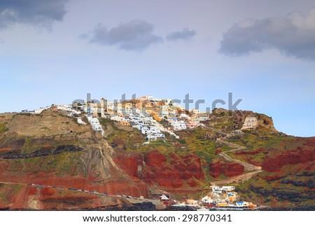 Oia village and harbor on top of volcanic rocks, Santorini island, Greece - stock photo