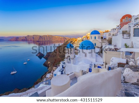 Oia village in the morning with dusk sky colors Santorini, Greece - Oia at morning, Santorini, Cyclades, Greece, Building lit up after sunrise in Oia, Santorini, Greece - stock photo