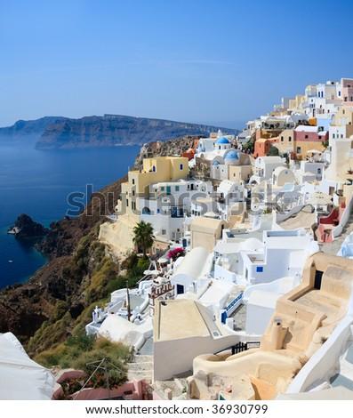 Oia village overlooks the spectacular caldera surrounding the beautiful island of Santorini, Greece - stock photo