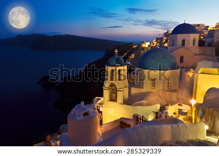Oia village with blue church domes at night at night, Santorini, Greece - stock photo