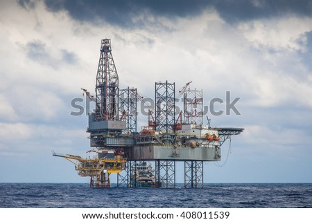Oil and gas drilling rig working on remote wellhead platform to drill the oil and gas reservoir - stock photo
