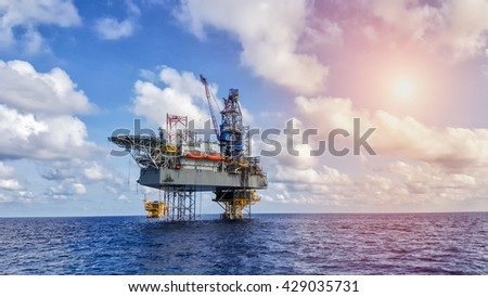 Oil and gas drilling rig working on remote wellhead platform to drill the oilfield reservoir industry - stock photo