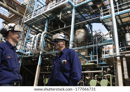 oil and gas engineers with pipelines and pumps in the background - stock photo