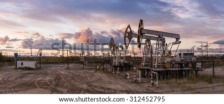 Oil and gas industry. Panoramic of a pump jack and oil refinery. - stock photo