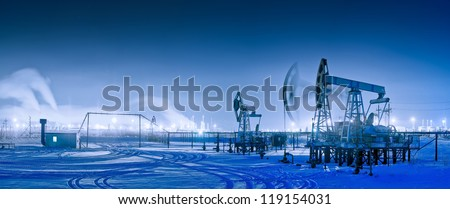 Oil and gas industry. Panoramic of a pump jack and oil refinery in the winter with snow. Night view. - stock photo