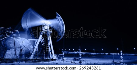Oil and gas industry. Panoramic of a pumpjack. Night view. - stock photo