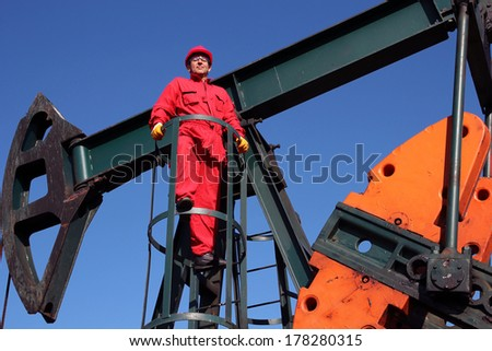 Oil and Gas Industry. Pump jack maintenance and repair. Worker in action at pump jack oil well.  - stock photo