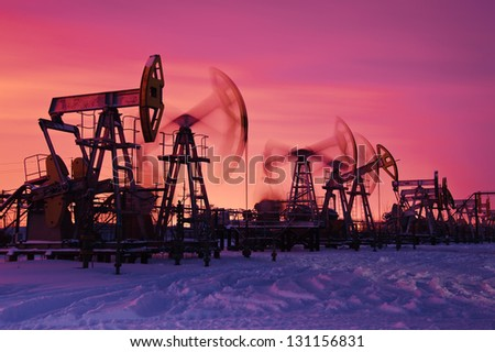 Oil and gas industry. Pump jacks at sunset sky background. - stock photo