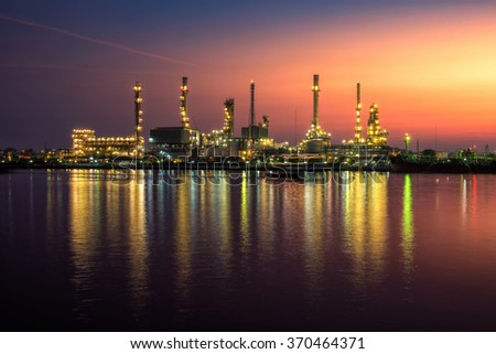 Oil and gas industry - refinery at Sunrise - factory - petrochemecal plant with reflection over the river - stock photo