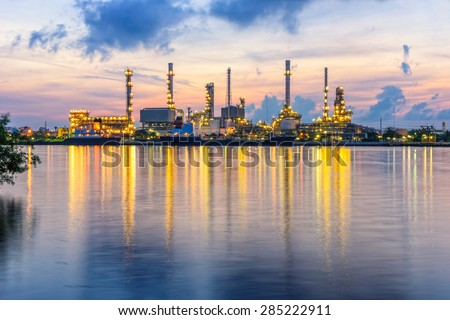 Oil and gas industry - refinery at sunrise - factory - petrochemical plantwith reflection over the river - stock photo