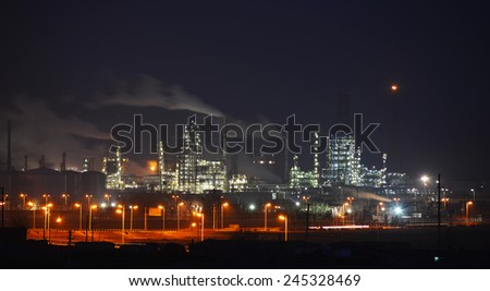Oil and gas industry refinery factory petrochemical plant lit up at night - stock photo