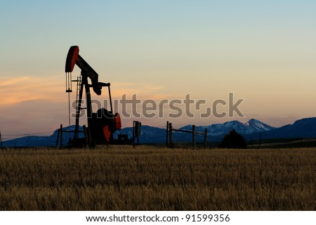Oil and gas industry. Silhouette of oil pump against a sunset sky - stock photo