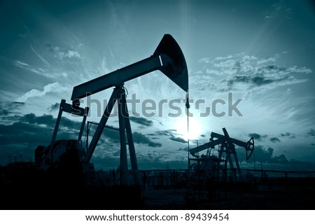 Oil and gas industry. Silhouette oil pumps on a sunset sky background. Toned. - stock photo