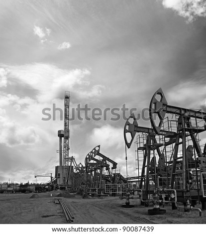 Oil and gas industry. Work of oil pump jack and rig on a oil field. Mining and drilling. Black and white photo - stock photo