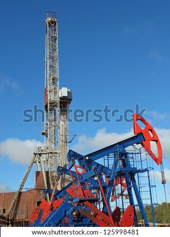 Oil and gas industry. Work of oil pump jack on a oil field. Borehole drilling oil well - stock photo