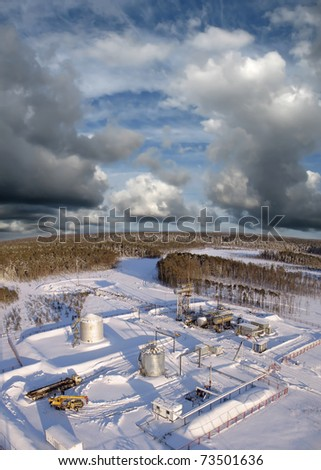 Oil and gas industry. Work of oil pump jack on a oil field.. Construction site in wild winter forest. Building of petrochemical plant. Panoramic view - stock photo