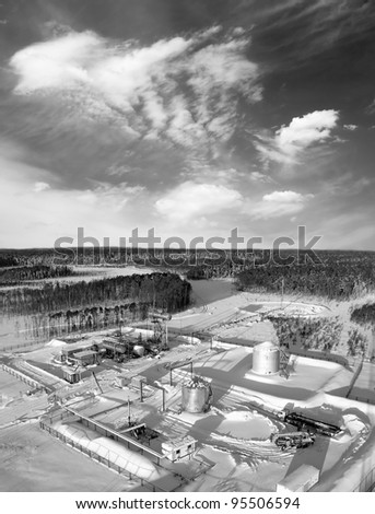 Oil and gas industry. Work of oil pump jack on a oil field. Construction site in wild winter forest. Building of petrochemical plant. Black and white photo. - stock photo